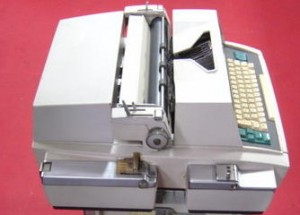 Terminal informatique équipé d'un perforateur/lecteur de ruban (au premier plan)