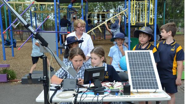 Photo montrant de jeunes écoliers et un système de suivi automatique des antennes. Le lien envoie vers la page décrivant cette réalisation.