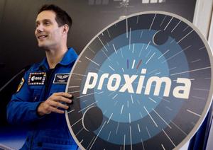 Photo de Thomas Pesquet tenant un écusson géant de la mission Proxima