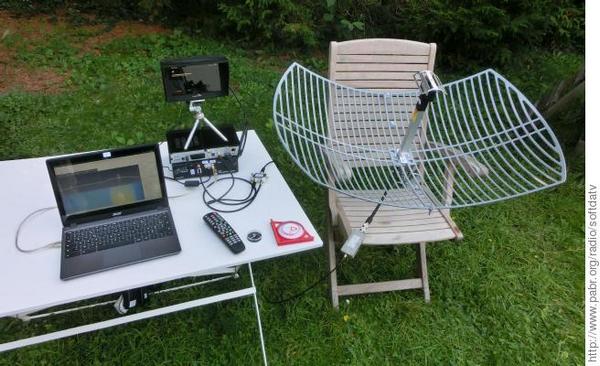 Image montrant un essai de réception DATV de l'ISS. La parabole est posée sur une chaise de jardin.